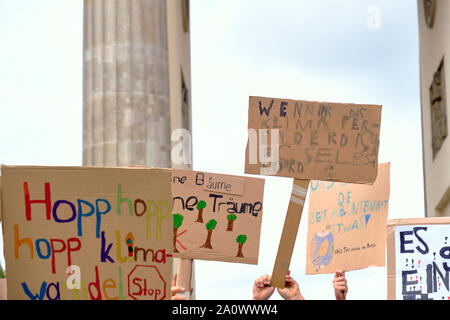 Global climate strike in Berlin, Germany, protesters with placards on a rally by Brandenburg Gate in German capital. - Stock Photo