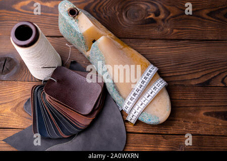 Leather samples for shoes and plastic shoe last on dark wooden table. Designer furniture clothes. Shoe maker workspace. - Stock Photo