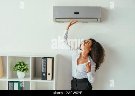 pretty african american businesswoman touching air conditioner while suffering from heat in office - Stock Photo