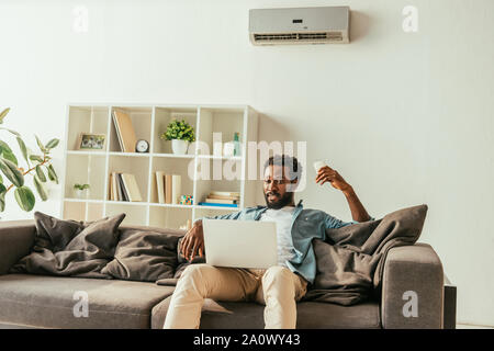 handsome african man using laptop while sitting on sofa under air conditioner and holding remote controller - Stock Photo