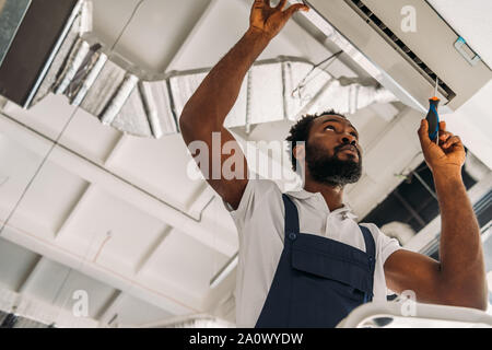 low angle view of african american handyman repairing air conditioner with screwdriver - Stock Photo