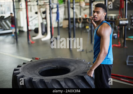Portrait of handsome muscular man looking at camera standing by heavy tire during cross training in modern gym, copy space