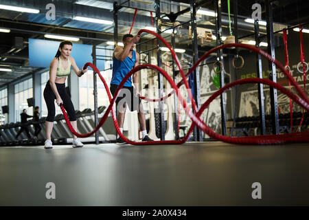Wide angle portrait of fit couple exercising with battle ropes during strength workout in cross functional gym, copy space