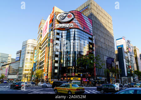 Tokyo, Sukiyabashi crossroads and the Hulic Ginza Building with the flagship Ginza Gap store. Cars driving past over pedestrian crossing. Daytime. - Stock Photo