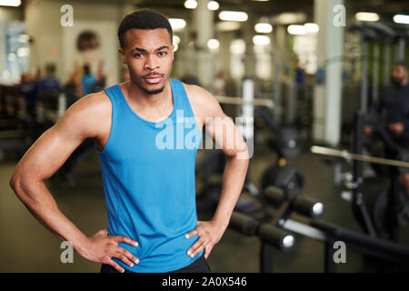 Waist up portrait of muscular fitness coach looking at camera while posing confidently in modern gym, copy space