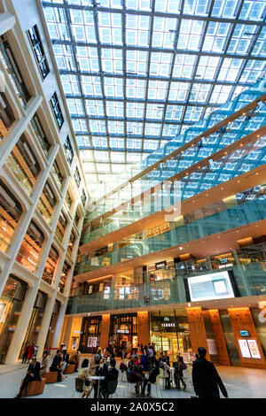 Tokyo, Marunouchi. JP tower KITTE building interior. The triangular atrium, floors of shops, roof and ground floor seating with people. Daytime. - Stock Photo