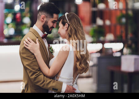 Stylish happy bride and groom posing at big love word in evening light at wedding reception outdoors. Gorgeous wedding couple of newlyweds having fun - Stock Photo
