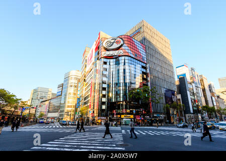 Tokyo, Sukiyabashi crossroads and the Hulic Ginza Building with the flagship Ginza Gap store. People crossing street on pedestrian crossing. Daytime. - Stock Photo