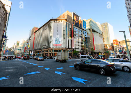 Tokyo, the Ginza 4 interchange with traffic going past and flagship Mitsukoshi department store opposite. Golden hour, late afternoon. Blue sky. - Stock Photo