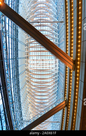 Japan, Tokyo International Forum. Interior. Glass metal framed roof seen from directly below with two overhead walkway bridges. Illuminated, blue hour