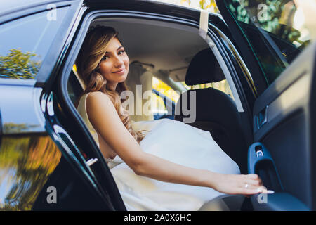 A bride takes pictures in the black car. - Stock Photo