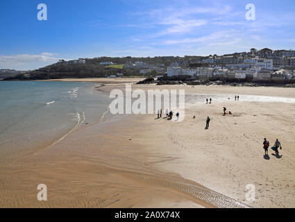 Visitors and residents walk along the beach at St Ives when the tide is out - Stock Photo