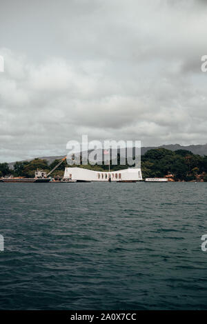 Pearl Harbor, Hawaii - August 23rd 2019: Mountain views in the background of the USS Arizona Memorial. Taken from Pearl Harbor National Memorial. - Stock Photo