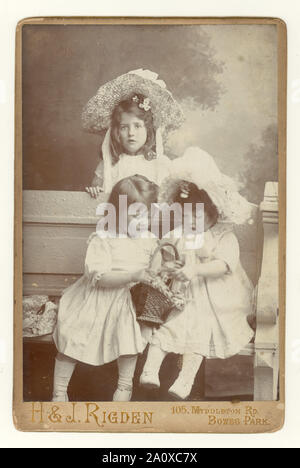 Original antique Edwardian cabinet card, charming studio portrait of three pretty young siblings, sisters, in summer clothes, wearing large straw hats and white smocks, Bowes Park, London, U.K. circa 1904.
