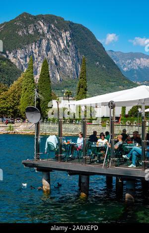 People eating at restaurant on platform above lake, Lake Garda, Riva del Garda, Trentino, Alto Adige, Northern Italy - Stock Photo