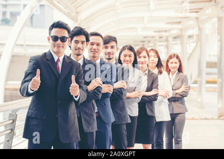 Business partners giving thumbs up after complete a deal to show potential of leadership with corporate partnership. Group of success business people - Stock Photo