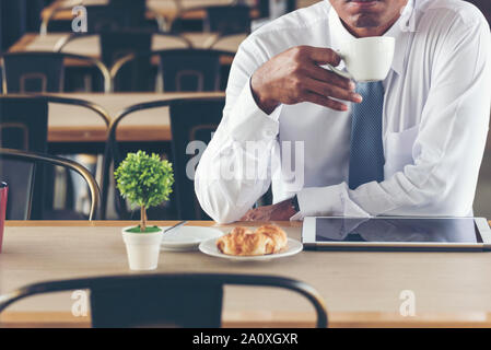 Asian Handsome businessman working outdoor in the coffee shop with laptop and holding cup of coffee on hand. Work outside office using technology with - Stock Photo