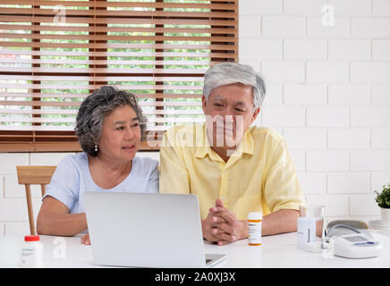 Asian couple seniors use laptop video conference with doctor about illness and prescription pill in living room at home.Healthy lifestyle.aging at hom - Stock Photo