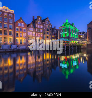 An evening in Amsterdam with the view towards The Grasshopper and the Oude Kerk (Old Church) in the background, oldest building in Amsterdam. - Stock Photo