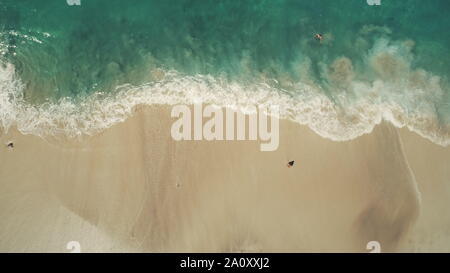 Top Down View: Ocean Beach Waves Break on White Sand. Crystal water landscape in Tropical Bali Island, Indonesia. Travel Vacation Recreation Paradise Tourism Concept. People swimming having fun - Stock Photo