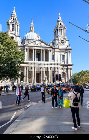 Tourists taking photographs in front of St Paul's Cathedral, London, UK - Stock Photo