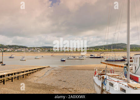 St George's Channel at Conwy.  Two boats are moored close to a slipway and others are afloat in the channel. A hill is in the distance and clouds are - Stock Photo