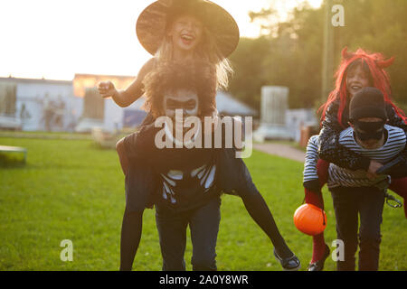 Portrait of carefree kids playing outdoors on Halloween and running towards camera laughing happily - Stock Photo