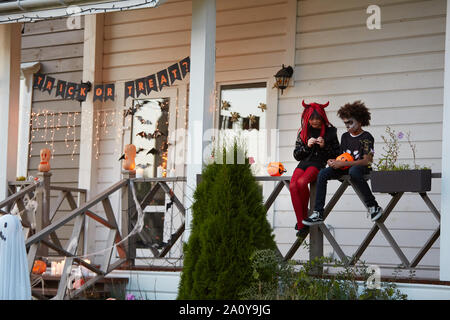 Wide angle view at boy and girl eating Halloween candy sitting on fence after trick or treating together, copy space - Stock Photo