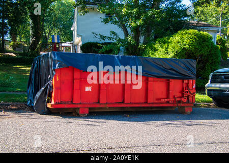 Red dumpster with black plastic liner on a asphalt street near the side of a house with trees in the background - Stock Photo