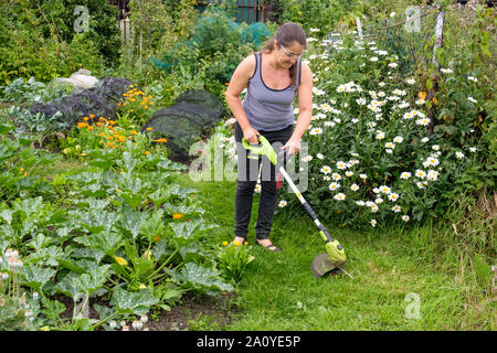 Woman using cordless (lithium-ion battery) strimmer to cut grass on path in allotment - Stock Photo