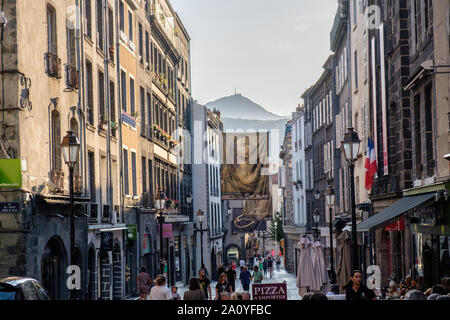 Evening view of restaurants down Rue des Gras looking towards le Puy de Dome in Clermont Ferrand, France - Stock Photo