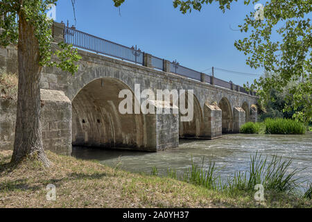 Bridge of the Nuns in the nineteenth-century classicist style over the Pisuerga River as it passes through the town of Alar del Rey, Palencia, Spain - Stock Photo
