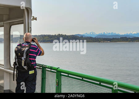 EN ROUTE SEATTLE TO BREMERTON - JUNE 2018: Person taking a picture from the deck of a passenger ferry on its way from Seattle to Bremerton. - Stock Photo