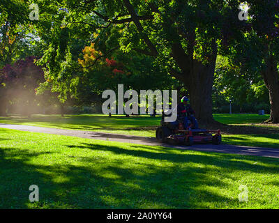 A ride-on lawn mower races down the path, trailing a cloud of dust in the early evening sun, Commissioners Park, Ottawa, Ontario, Canada. - Stock Photo