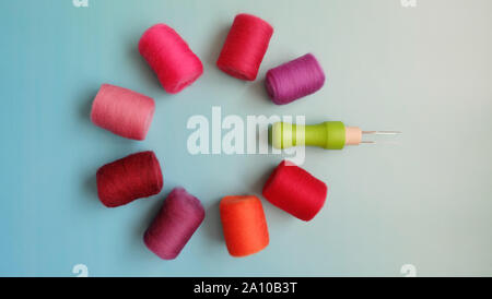Flat lay of red and pink felt wool rolls and felt needle arranged in a circle. - Stock Photo