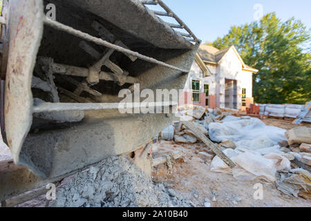 Close-up of cement mixer used when laying bricks during new home construction. - Stock Photo
