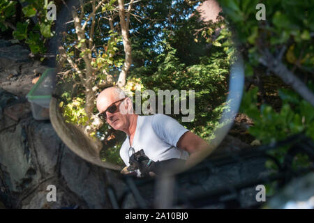 The reflection of a man can be seen in this motorcycle mirror in San Rafael, CA. - Stock Photo