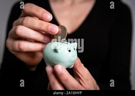 Savings and finance concept. Putting euro coin in small piggy bank - Stock Photo