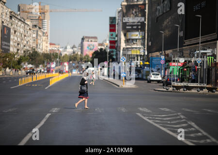 Bucharest, Romania - September 22, 2019: People walk on an empty boulevard (usually with heavy traffic) during the World Car Free Day. - Stock Photo