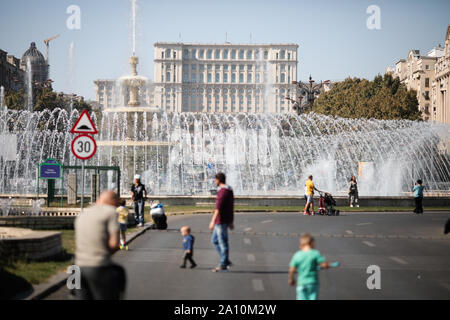 Bucharest, Romania - September 22, 2019: People walk on an empty boulevard with the Palace of Parliament on the background in downtown Bucharest. - Stock Photo