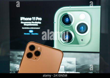 Shanghai, China. 23rd Sep, 2019. In this photo illustration a back side of an iPhone 11 Pro Max smartphone, which features a triple-camera design, is seen in front of a computer screen displaying Apple's homepage of the iPhone 11 Pro. Credit: Alex Tai/SOPA Images/ZUMA Wire/Alamy Live News - Stock Photo