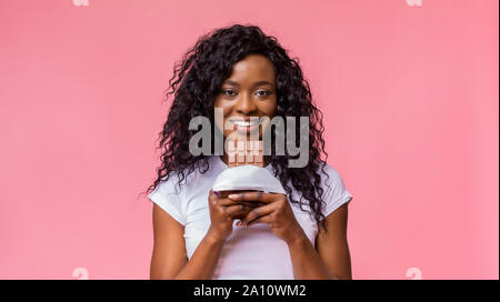 Black woman want to eat chocolate, smiling at camera - Stock Photo