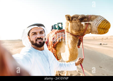Man wearing traditional clothes, taking a camel out on the desert sand, in Dubai - Stock Photo