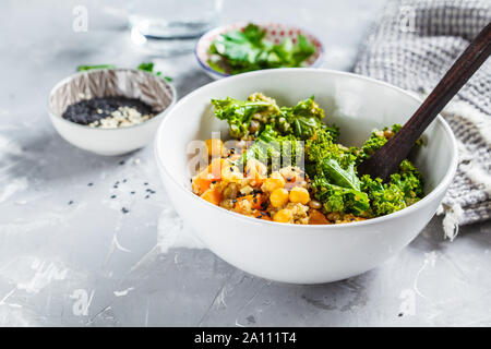 Vegan stew with chickpeas, sweet potato and kale in a white bowl. - Stock Photo