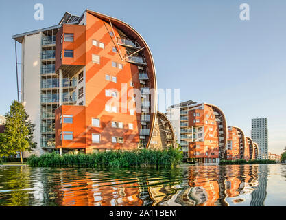 Den Bosch, The Netherlands, September 20, 2019: row of sailboat-inspired residential buildings, reflecting in the adjacent pond in the golden hour on - Stock Photo
