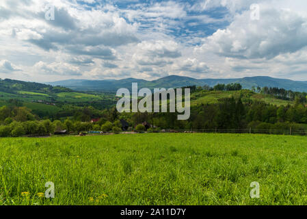 beautiful springtime surrounding of Vendryne village in Czech republic with meadows, hills of Slezske and Moravskoslezske Beskydy mountains and disper - Stock Photo