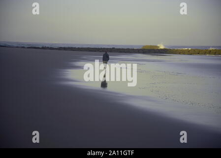 Man walking along a beach in south-West France, pasakdek - Stock Photo