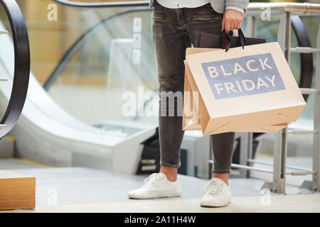 Low section portrait of fashionable man wearing jeans and holding shopping bags with Black Friday inscription standing against escalator in mall, copy space - Stock Photo