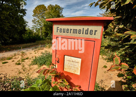 Nuremberg, Germany - September 23, 2019: An old red fire alarm that ist out of service is standing on an abandoned property between trees and hedges - Stock Photo