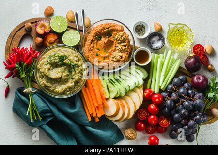 veggie serving table with snacks with vegetables, fruits, baba ganoush and dip or spread of roasted red pepper and nuts. healthy vegan food for celebr - Stock Photo